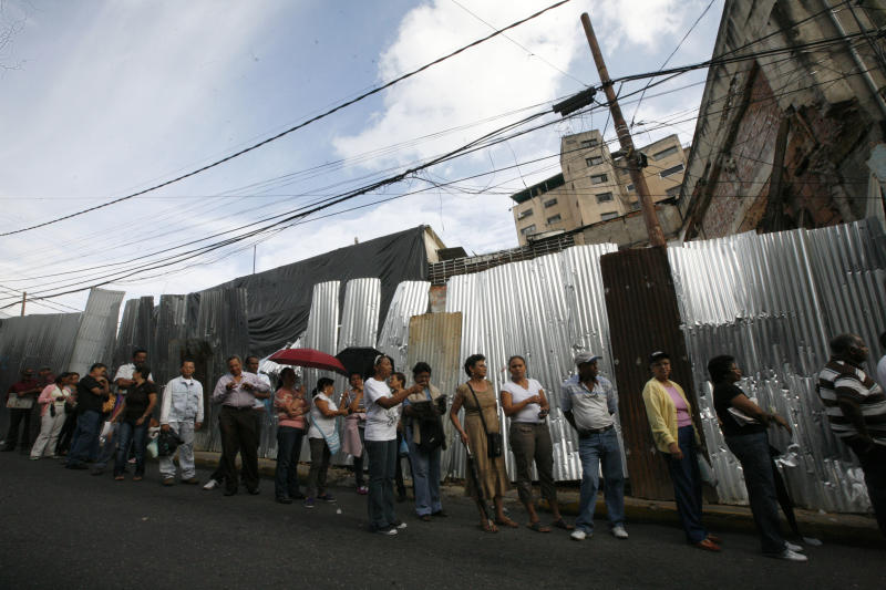 Residents line up at a polling station during the presidential election in the Petare neighborhood of Caracas, Venezuela, Sunday, Oct. 7, 2012. President Hugo Chavez is running for re-election against opposition candidate Henrique Capriles. (AP Photo/Ariana Cubillos)