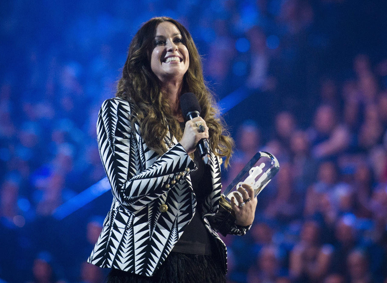 """In this March 15, 2015, file photo, singer Alanis Morissette receives her achievement from the Canadian Music Hall of Fame during the 2015 Juno Awards in Hamilton, Ont. Celebrities including Nicky Minaj and Morissette are among the victims of what police suspect is """"flocking,"""" so named because gang members flock like birds to areas where home burglaries provide the biggest payoff. Morissette had about $2 million in jewelry and valuables stolen from her Brentwood mansion. (Nathan Denette/The Canadian Press via AP)"""