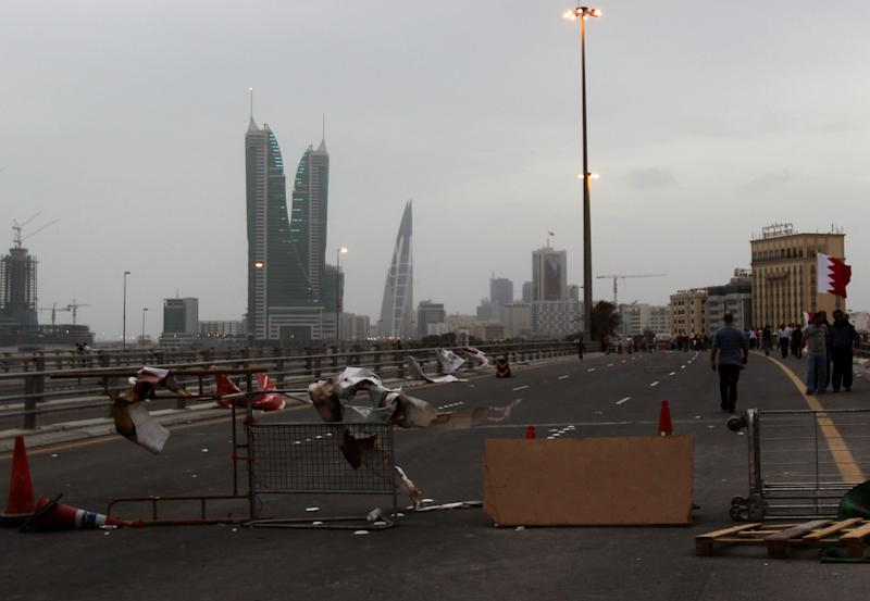 A barricade set up by Bahraini anti-government protesters Sunday, March 13, 2011, prevents traffic from entering the capital of Manama, Bahrain, with the skyscrapers of its financial district seen in the background. The demonstrators set up the barricade after riot police left the area, failing to dislodge them with rubber bullets and tear gas from their encampment at Pearl roundabout. (AP Photo/Hasan Jamali)