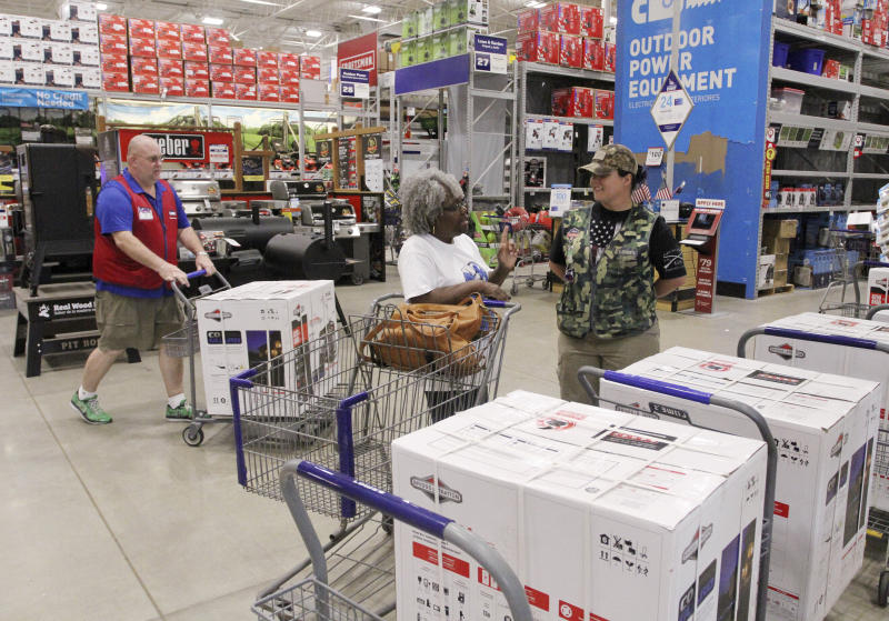 FILE - In this Sept. 3, 2019, file photo store associates help customers with generators and supplies at Lowes in New Bern, N.C., as residents bracing for potential storm weather. Backup power options range from gasoline-powered portable generators, which can cost $1,000 or more, to solar panels plus batteries, which cost tens of thousands of dollars to purchase and install. (Gray Whitley/Sun Journal via AP, File)