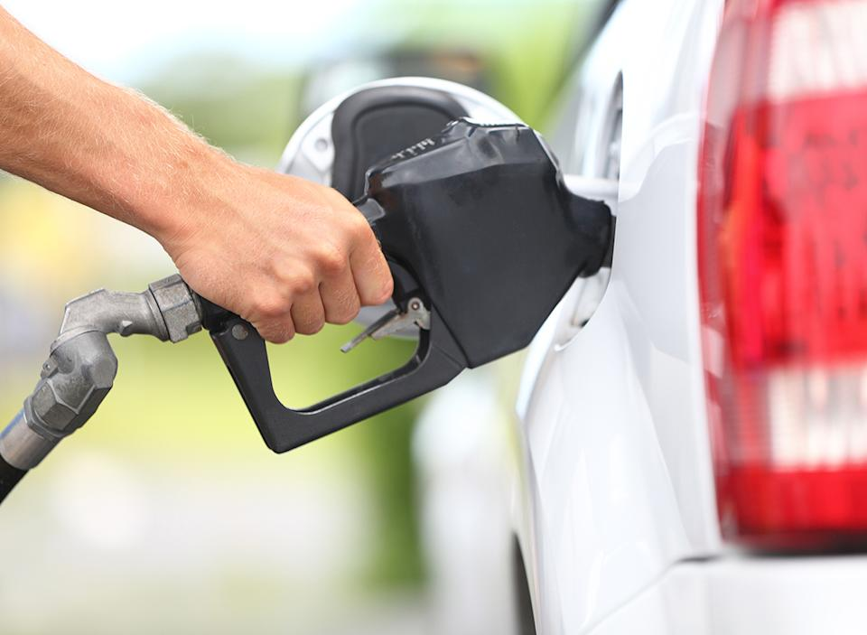 man pumping gas into car