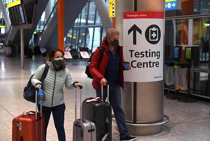 <p>A sign directs passengers to a Covid-19 testing centre at Terminal 5 of Heathrow Airport</p> (AFP/Getty)