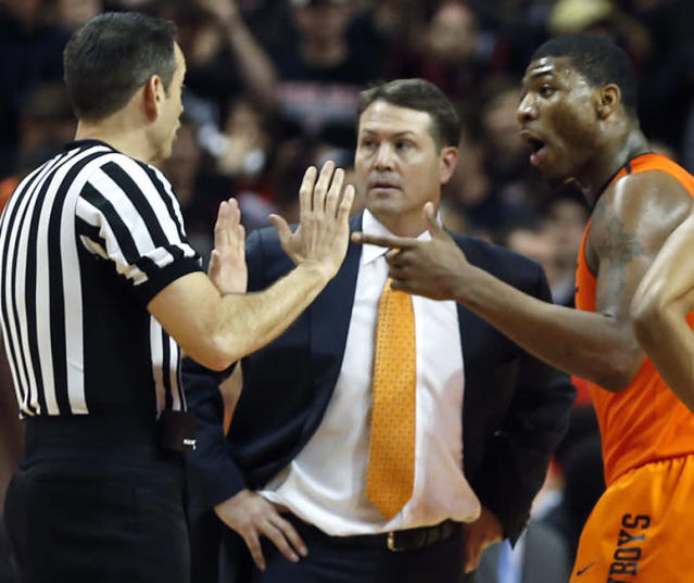 Oklahoma State head coach Travis Ford, center, Marcus Smart and Markel Brown, right, talk to the referee after Smart shoved a fan during an NCAA college basketball game against Texas Tech, Saturday, Feb, 8, 2014, in Lubbock, Texas. (AP Photo/Lubbock Avalanche-Journal, Tori Eichberger)