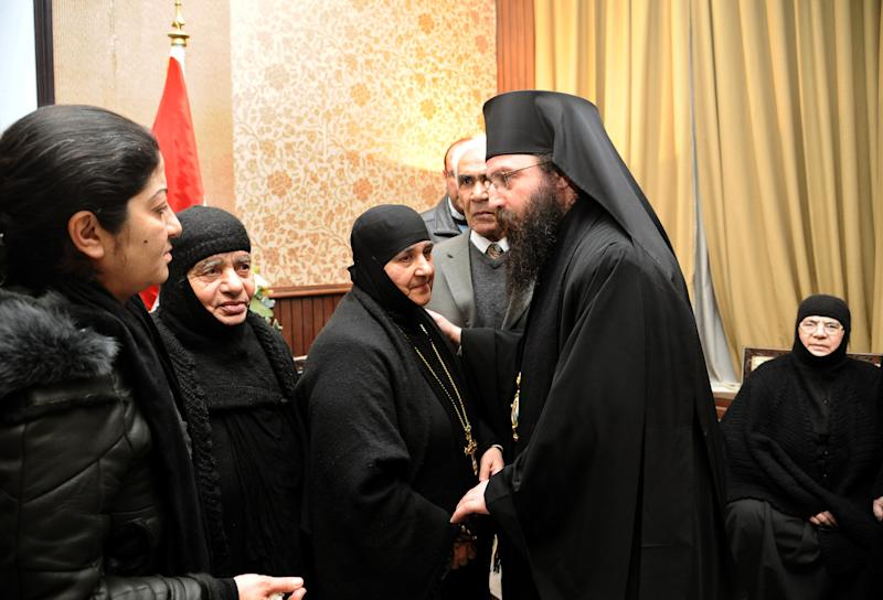 In this photo released by the Syrian official news agency SANA, a group of nuns who were freed after being held by Syrian rebels, greet church officials at the Syrian border town of Jdeidat Yabous, early Monday, March. 10, 2014. Rebels in Syria freed more than a dozen Greek Orthodox nuns on Monday, ending their three-month captivity in exchange for Syrian authorities releasing dozens of female prisoners. The release of the nuns and their helpers, 16 women in all, is a rare successful prisoner-exchange deal between Syrian government authorities and the rebels seeking to overthrow the rule of President Bashar Assad. (AP Photo/SANA)