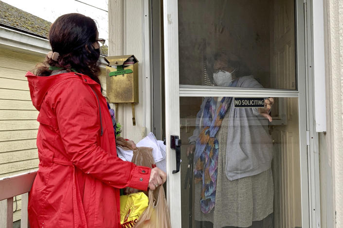 Senior citizen Barbara Bender answers the door for Store to Door employee Nancy Murphy in Portland, Ore., as she delivers an order of groceries for the nonprofit on Feb. 25, 2021. An untold number of older people are getting left behind in the desperate dash for shots because they are too frail, overwhelmed, isolated or poor to navigate a system that favors healthier individuals with more resources. Nonprofits, churches and health care outreach workers are scrambling to to reach older people who are falling through the cracks before the nation's focus moves on and the competition for vaccines stiffens. (AP Photo/Gillian Flaccus)