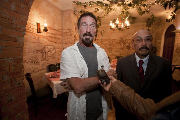 """Software company founder John McAfee, left, accompanied by his lawyer Telesforo Guerra, right, answers questions during an interview at a local restaurant in Guatemala City, Tuesday, Dec. 4, 2012. McAfee, 67, has been identified as a """"person of interest"""" in the killing of his neighbor in Belize, 52-year-old Gregory Faull. Police are urging McAfee to come in for questioning. The anti-virus company founder fled Belize and is seeking political asylum in Guatemala, according to his lawyer Telesforo Guerra. (AP Photo/Moises Castillo)"""