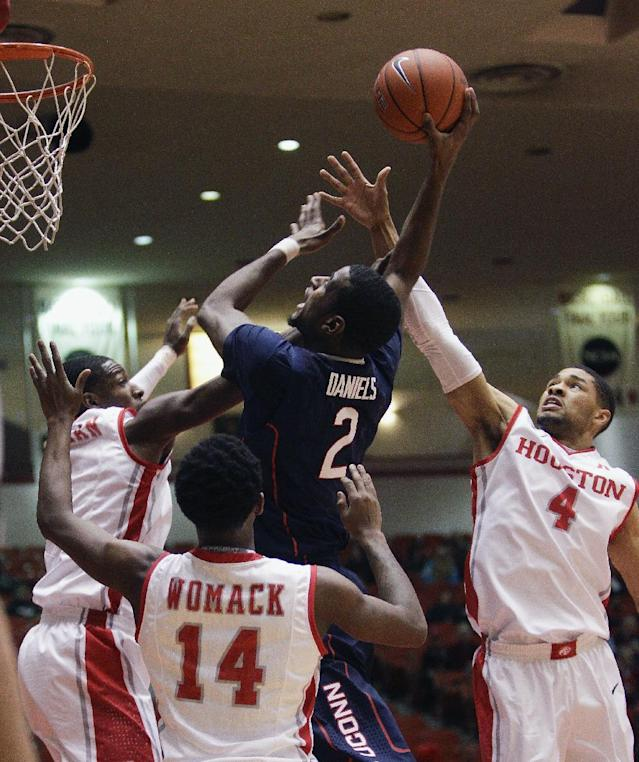 Connecticut forward DeAndre Daniels (2) shoots as Houston's LeRon Barnes, left, LeRon Barnes (4) and Tione Womack (14) defend during the first half of an NCAA college basketball game Tuesday, Dec. 31, 2013, in Houston. (AP Photo/Bob Levey)