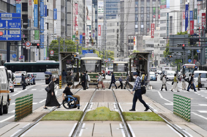 People wearing face masks make their way in Hiroshima, western Japan, Friday, May 14, 2021. Japan is set to further expand a coronavirus state of emergency, currently in Tokyo and five other prefectures, to nine areas, including HIroshima, as the government is determined to hold the Olympics in just over two months. (Shingo Nishizume/Kyodo News via AP)