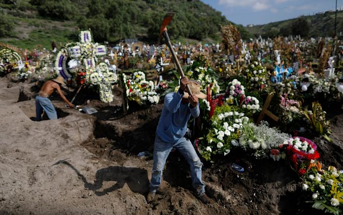 On the outskirts of Mexico City, workers dig fresh graves in a section of the municipal cemetery of Valle de Chalco, which opened three months ago to accommodate the surge in deaths during the pandemic - Rebecca Blackwell/AP