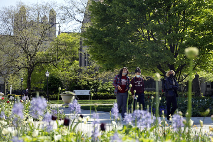 Students wearing masks make their way through the University of Chicago campus, Thursday, May 6, 2021, in Chicago. Even as restrictions relax across much of the United States, colleges and universities have taken new steps to police campus life as the virus spreads through students who are among the last adults to get access to vaccines. (AP Photo/Shafkat Anowar)