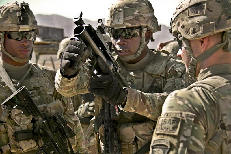 U.S. Army Pfc. Rohan Wright, center, a cavalry scout with a personal security detachment with the 4th Brigade Combat Team, 101st Airborne Division, prepares to fire an M320 Grenade Launcher Module (GLM) at the weapons range at Forward Operating Base Thund