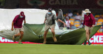 Ground staff bring covers onto the field as rain stops play on day four of the fourth cricket test between India and Australia at the Gabba, Brisbane, Australia, Monday, Jan. 18, 2021. (AP Photo/Tertius Pickard)