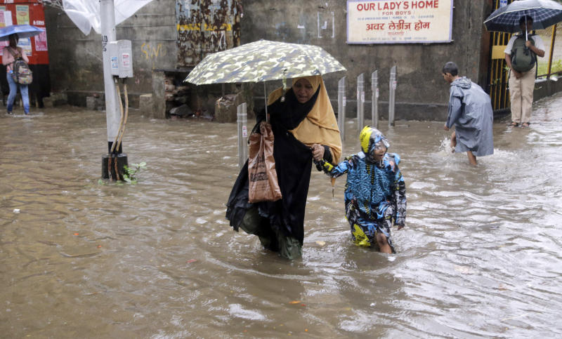 A woman holds the hand of a child and wades through a waterlogged street following rainfall in Mumbai, India, Friday, June 28, 2019. India receives its monsoon rains from June to October. (AP Photo/Rajanish Kakade)