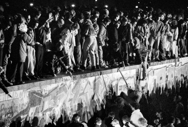 East and West German citizens celebrate as they climb the Berlin Wall at the Brandenburg Gate after the opening of the East German border was announced in Berlin, Nov. 9, 1989. (Photo: Fabrizio Bensch/Reuters)