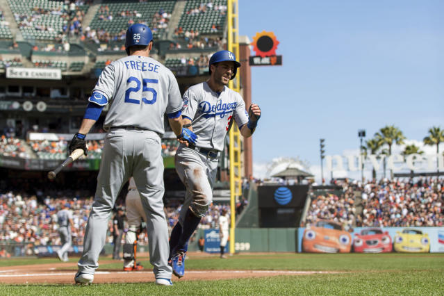 Los Angeles Dodgers Chris Taylor, right, celebrates with David Freese after scoring a run against the San Francisco Giants in the first inning of a baseball game in San Francisco, Sunday, Sept. 30, 2018. (AP Photo/John Hefti)