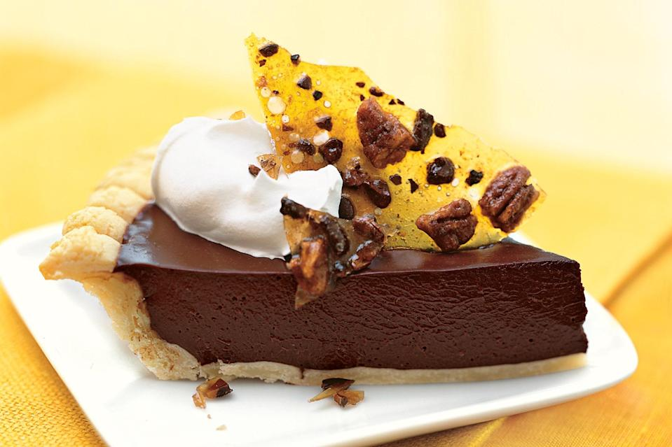 """Cocoa nibs add crunch and extra deep chocolate flavor to this decadent pie. <a href=""""https://www.epicurious.com/recipes/food/views/dark-chocolate-pie-with-cocoa-nib-praline-233725?mbid=synd_yahoo_rss"""" rel=""""nofollow noopener"""" target=""""_blank"""" data-ylk=""""slk:See recipe."""" class=""""link rapid-noclick-resp"""">See recipe.</a>"""