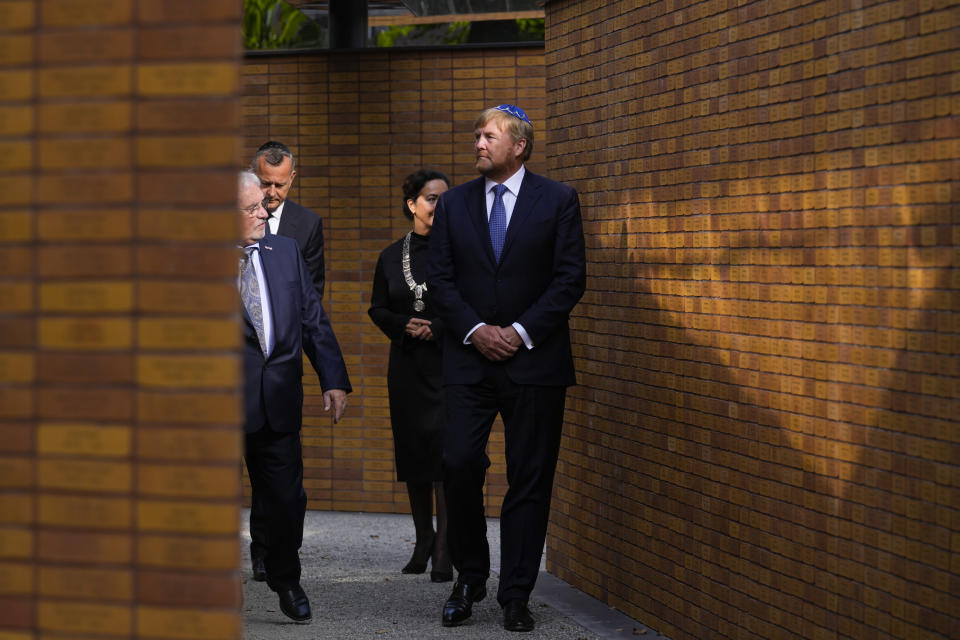 """King Willem-Alexander, right, walks along walls with name stones after officially unveiling a new monument in the heart of Amsterdam's historic Jewish Quarter on Sunday, Sept. 19, 2021, honoring the 102,000 Dutch victims of the Holocaust. Designed by Polish-Jewish architect Daniel Libeskind, the memorial is made up of walls shaped to form four Hebrew letters spelling out a word that translates as """"In Memory Of."""" The walls are built using bricks each of which is inscribed with the name of one of the 102,000 Jews, Roma and Sinti who were murdered in Nazi concentration camps during World War II or who died on their way to the camps. (AP Photo/Peter Dejong)"""