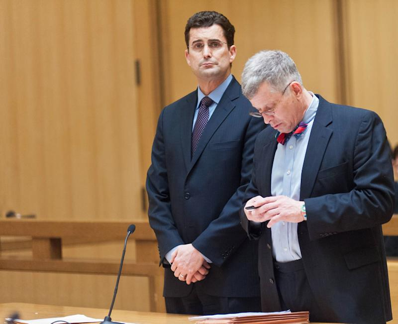 "WCBS Television anchorman Rob Morrison, left, listens as his attorney Robert Skovgaard checks a cell phone during his arraignment in Superior Court on Tuesday Feb. 19, 2013 in Stamford, Conn. Morrison was arrested Monday night on charges of attacking his wife, Ashley Morrison, at their Connecticut home. He is charged with strangulation, threatening and disorderly conduct and ordered to to stay 100 yards away from his wife except when they're both at work. Ashley Morrison works for ""CBS Moneywatch."" (AP Photo/New York Daily News, David Handschuh, Pool)"