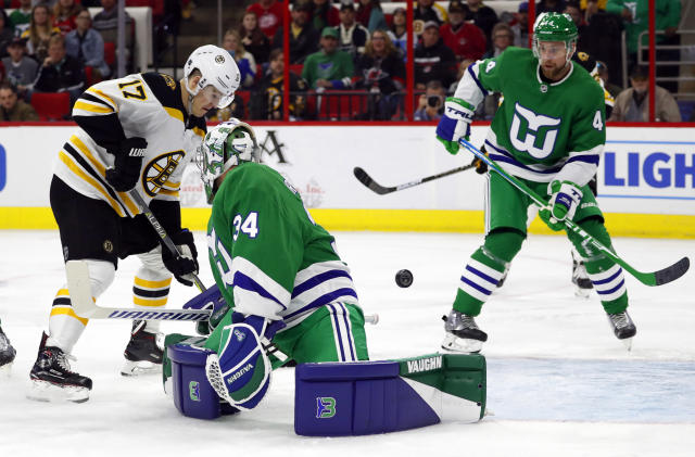 Boston Bruins' Ryan Donato (17) pushes the puck past Carolina Hurricanes goaltender Petr Mrazek (34) with Calvin de Haan (44) nearby during the first period of an NHL hockey game, Sunday, Dec. 23, 2018, in Raleigh, N.C. (AP Photo/Karl B DeBlaker)