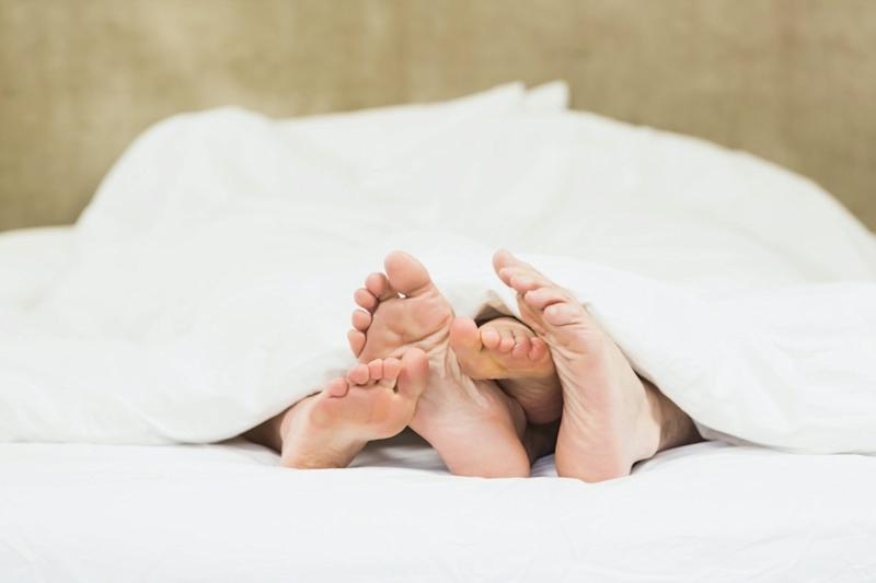 Close up of couple's feet in their bed