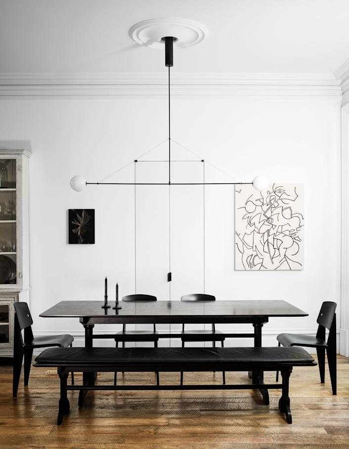 "<div class=""caption""> Jean Prouvé chairs surround the dining area's matter made table; <a href=""https://michaelanastassiades.com/"" rel=""nofollow noopener"" target=""_blank"" data-ylk=""slk:Michael Anastassiades"" class=""link rapid-noclick-resp"">Michael Anastassiades</a> chandelier; art by Chris Duncan (left) and Zio Ziegler (right); <a href=""https://www.farrow-ball.com/en-us"" rel=""nofollow noopener"" target=""_blank"" data-ylk=""slk:Farrow & Ball"" class=""link rapid-noclick-resp"">Farrow & Ball</a> wall paint. </div> <cite class=""credit"">Douglas Friedman</cite>"