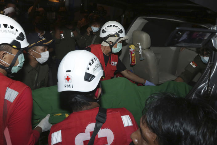 Rescuers carry the body of a victim of the sinking ferry KMP Yunice on a stretcher into a car in Banyuwangi, East Java, Indonesia, early Wednesday, June 30, 2021. Rescuers searched into the night Tuesday for several missing people after the ferry sank in rough seas near Indonesia's resort island of Bali, killing a number of people, officials said. (AP Photo)