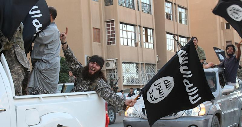 The black flag is waved by the Islamic State group in the northern rebel-held Syrian city of Raqa, in this image provided Jihadist media outlet Welayat Raqa