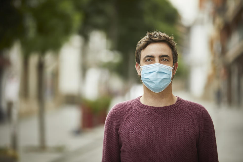 Portrait of a mature man standing on the street wearing a protective face mask for the coronavirus pandemic.