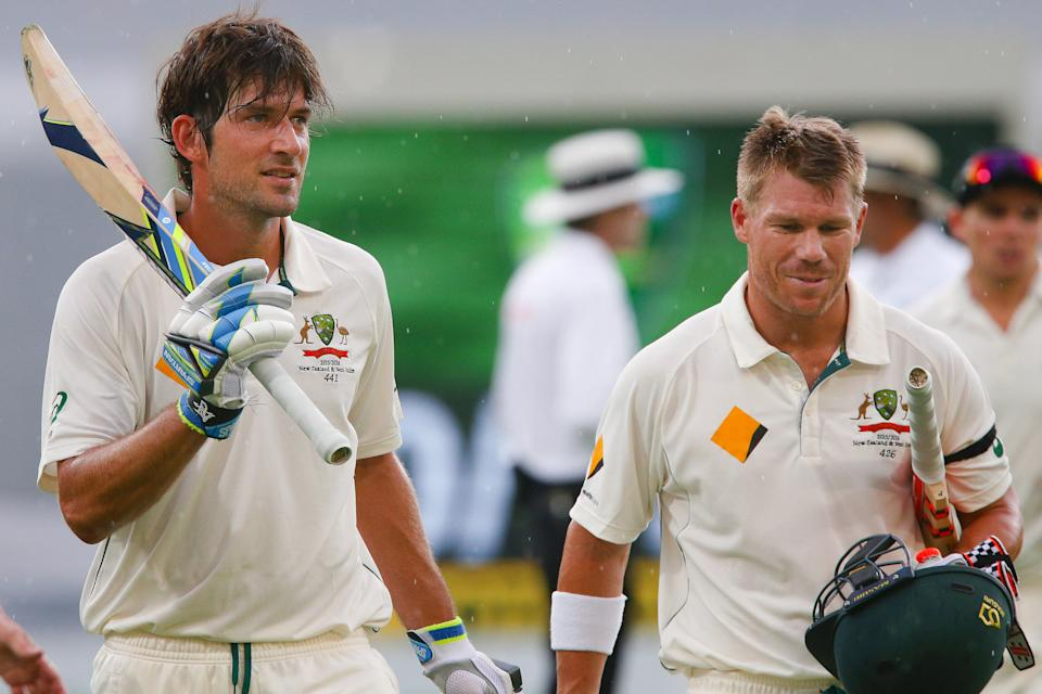 Australian batsman Joe Burns (pictured left) celebrates his maiden test century with opening partner David Warner (pictured right) as they walk off due to weather.