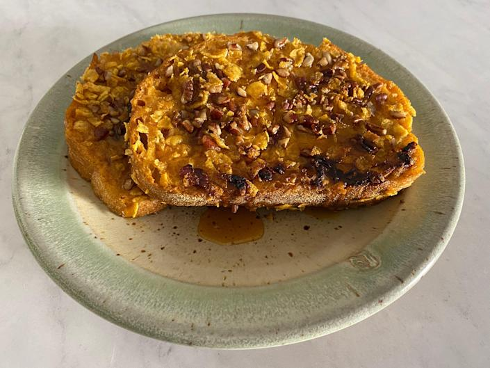 Pumpkin pecan and maple syrup French toast pieces on a green and beige plate