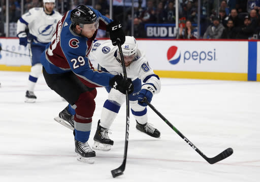 FILE - Colorado Avalanche center Nathan MacKinnon, front, fires the puck as Tampa Bay Lightning defenseman Erik Cernak covers in the first period of an NHL hockey game in Denver, in this Monday, Feb. 17, 2020, file photo. With MacKinnon, one of the top playmakers in the league, and Cale Makar, the defensive phenom whos coming off a rookie-of-the-year campaign, they're no longer that plucky, youthful team filled with speed and potential.(AP Photo/David Zalubowski, File)