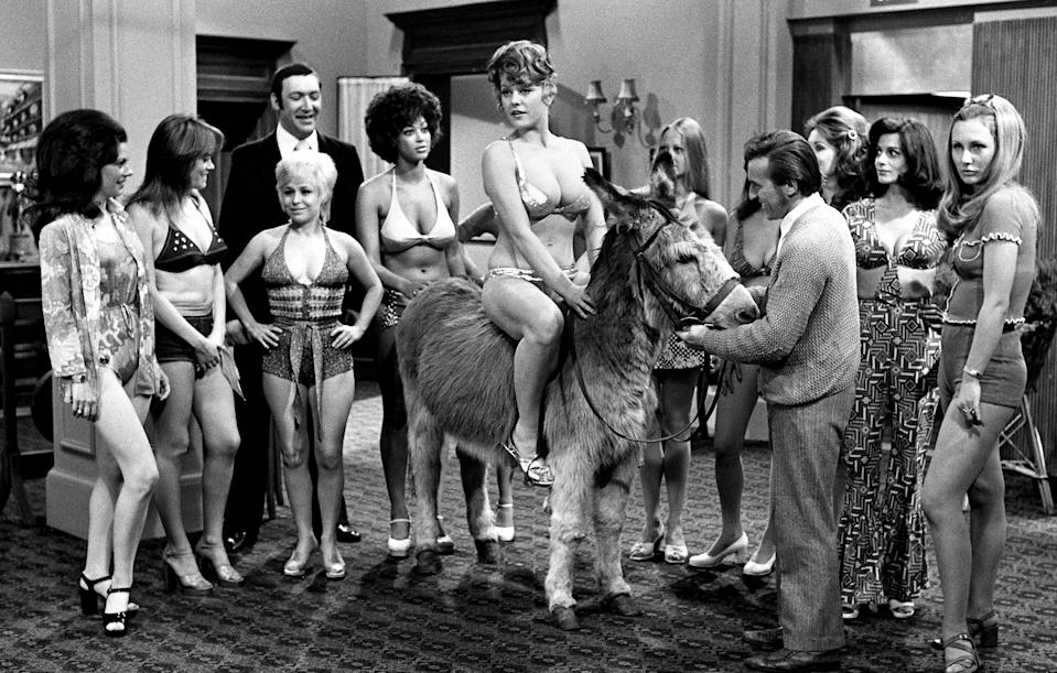 English actor Bernard Bresslaw (1934 - 1993) and actresses Wendy Richard and Barbara Windsor help orchestrate a beauty contest in the film 'Carry On Girls', 1973. Glamour model and actress Margaret Nolan is sitting astride the donkey. (Photo by Larry Ellis Collection/Getty Images)