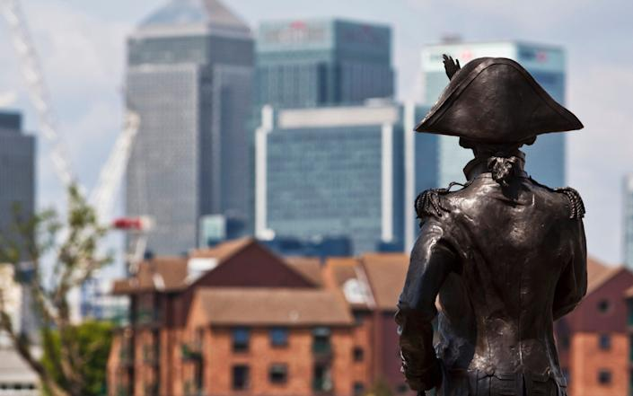 A statue of Lord Nelson in Greenwich, with Canary Wharf in the distance - bridgeman