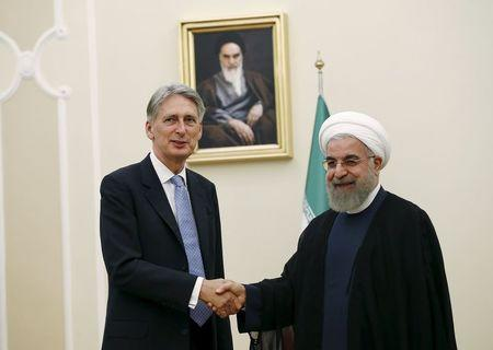 Britain's Foreign Secretary Hammond shakes hands with Iran's President Rouhani before a meeting at the President's Palace in Tehran