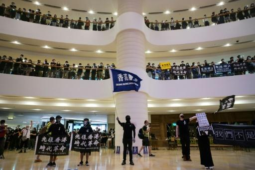 Protesters shout slogans at an upmarket shopping mall in Hong Kong on the anniversary of when a man fell to his death there after hanging a democracy banner
