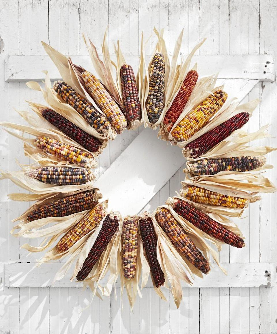 """<p>Nothing says """"fall"""" quite like flint corn. Here, it's dried and assembled into a gorgeous wreath.</p><p><strong>Make the wreath:</strong> Detach husks from one side of 20 medium-size Indian corn. Hot-glue the undersides of the corn to their husks. Lay out the corn in a circle with the tops pointing out, alternating colors. Hot-glue the corn to an 18-inch craft ring, and fill in any sparse areas with extra husks. </p>"""