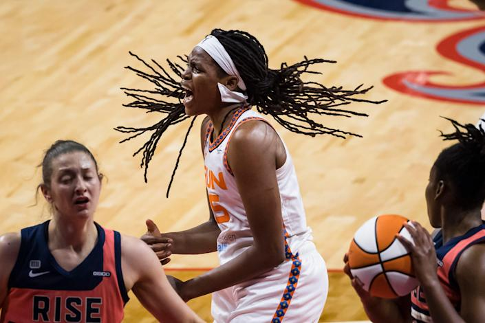 A basketball player stands open-mouthed as players stand to her either side.