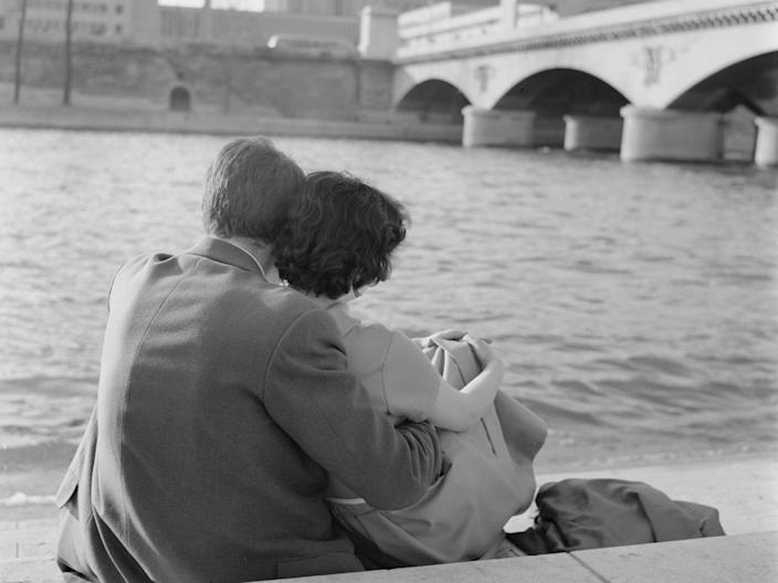 A young couple on the banks of the River Seine in Paris, France, in the spring, April 1958.