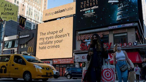PHOTO: People walk past digital billboards display 'stop asian hate' messages near Penn Station in New York, March 30, 2021. (Alexi Rosenfeld/Getty Images, FILE)