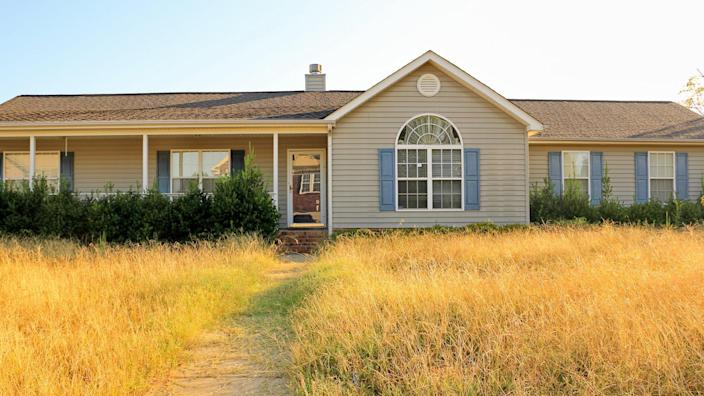 All too common scene of an unkempt,  ranch style, home in the foreclosure process in a working class subdivision in the United States, with overgrown yard and bushes making it an eyesore to the neighborhood.
