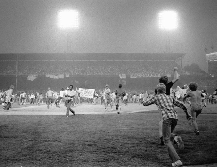 FILE - In this July 12, 1979, file photo, fans storm the field at Chicago's White Sox Park on Disco Demolition night after the first game of a doubleheader between the White Sox and Detroit Tigers. The promotion by a local radio station turned into a melee after hundreds of disco records were blown up on the field. The second game of the doubleheader was called by umpires who declared the field unfit for play. (AP Photo/Fred Jewell, File)