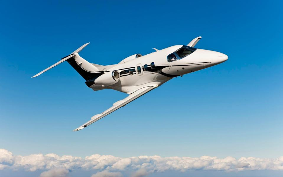 Pilots flying corporate jet above the clouds in clear blue skies. - RaptTV/Corbis RF Stills