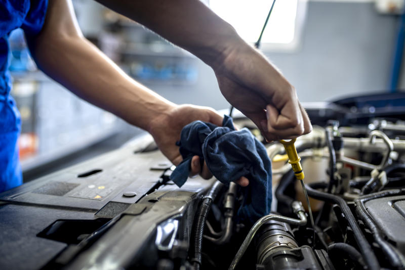 """Photo of Unrecognizable male mechanic measuring the oil level of an engine at an auto shop. Mechanic checking the oil level in a car service garage. Repairing engine at a service station. Car repair.""""r""""n."""