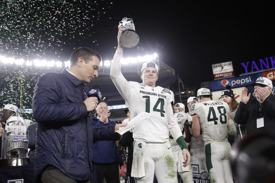 Michigan State's Brian Lewerke holds the Most Valuable Player trophy after the team's Pinstripe Bowl NCAA college football game against Wake Forest on Friday, Dec. 27, 2019, in New York. Michigan State won 27-21. (AP Photo/Frank Franklin II)