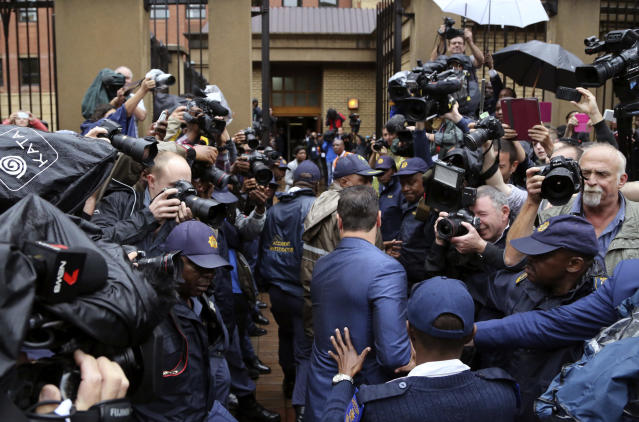 Carl Pistorius, at center in blue suit, the brother of Oscar Pistorius is escorted by police as he arrives at the high court in Pretoria, South Africa, Monday, March 3, 2014. Oscar Pistorius is charged with murder with premeditation in the shooting death of girlfriend Reeva Steenkamp in the pre-dawn hours of Valentine's Day 2013. (AP Photo/Schalk van Zuydam)