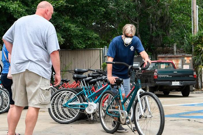 David Fleming, manager at Sharky's Bike Rental on Pope Avenue adjusts a seat for Cincinnati resident Perry Herbert, left and his wife Karen Herbert on Saturday, June 27, 2020 on Hilton Head Island. Fleming said about 50 percent of the customers wore a face covering, which he preferred. While the Ohioans weren't actively wearing a mask outdoors, the visitors were carrying masks to wear when entering businesses.