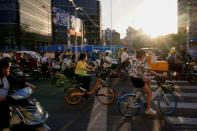 People ride bicycles and motorbikes on a street, amid the coronavirus disease pandemic, in Shanghai