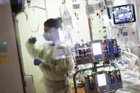 FILE - In this Aug. 31, 2021, file photo, Ann Enderle R.N. attends to a COVID-19 patient in the Medical Intensive care unit (MICU) at St. Luke's Boise Medical Center in Boise, Idaho. COVID-19 deaths in the U.S. have climbed to an average of more than 1,900 a day for the first time since early March, with experts saying the virus is preying largely on a select group: 71 million unvaccinated Americans. (AP Photo/Kyle Green, File)