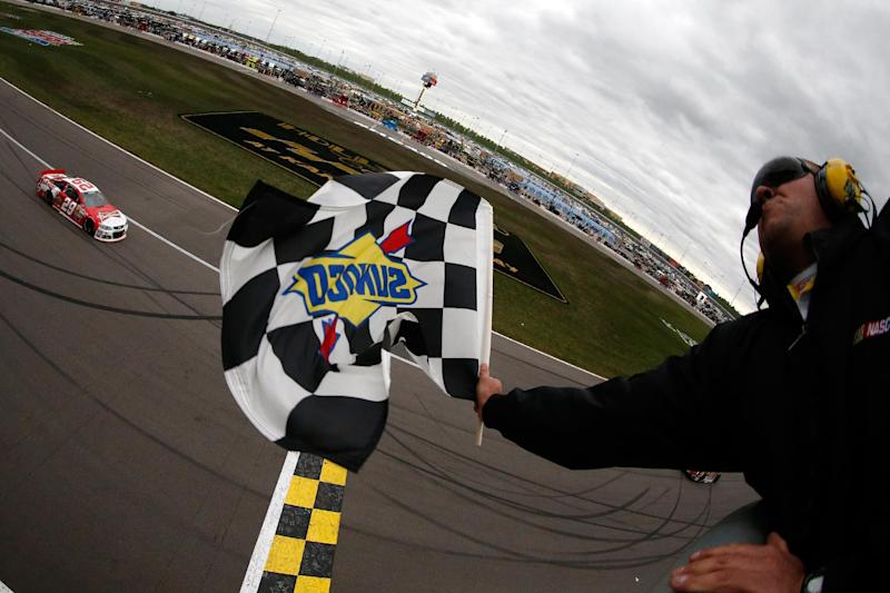 Driver Kevin Harvick (29) takes the checkered flag to win a NASCAR Sprint Cup series auto race at Kansas Speedway in Kansas City, Kan. (AP Photo/Chris Graythen, Pool)