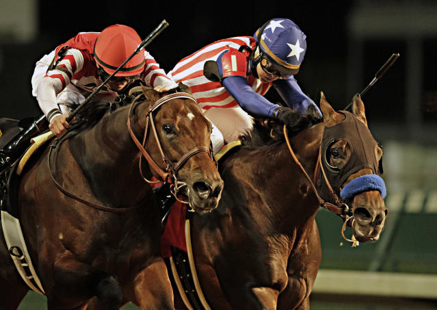 Favored Bayern, right, ridden by jockey Rosie Napravnik, battles Embellishing Bob, left, ridden by Brian Hernandez Jr., at the wire in the Derby Trial horse race at Churchill Downs in Louisville, Ky., Saturday, April 26, 2014. Bayern finished first but was disqualified and placed second for interference in the stretch and Embellishing Bob was awarded the victory. (AP Photo/Garry Jones)